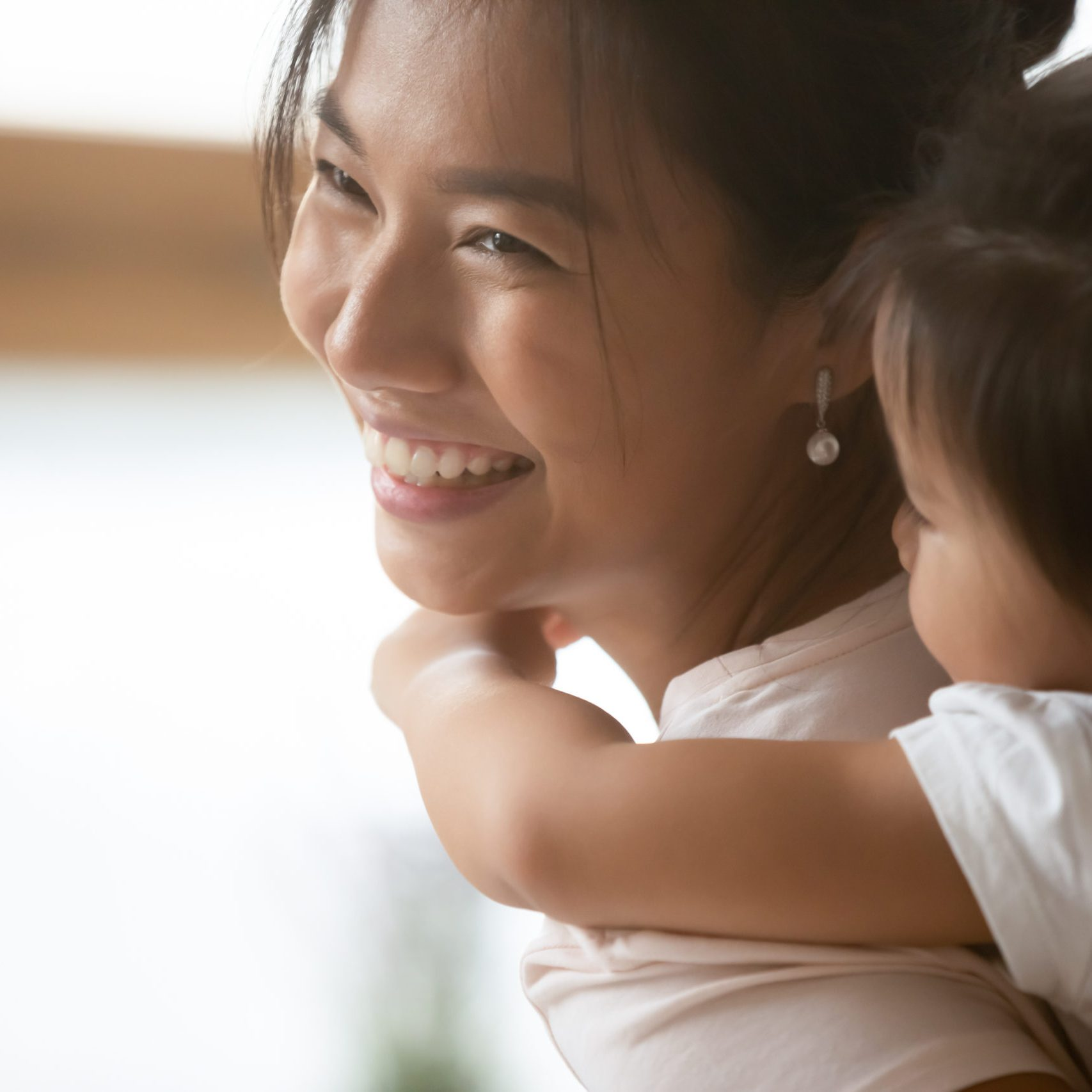 Close up head shot happy young asian ethnicity woman carrying on back cute little baby daughter, smiling biracial female nanny playing with adorable small kid girl indoors, daycare custody concept.